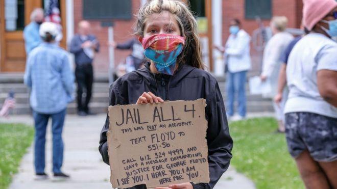"""Mujer con un cartel que dice """"encarcelen a los 4"""""""