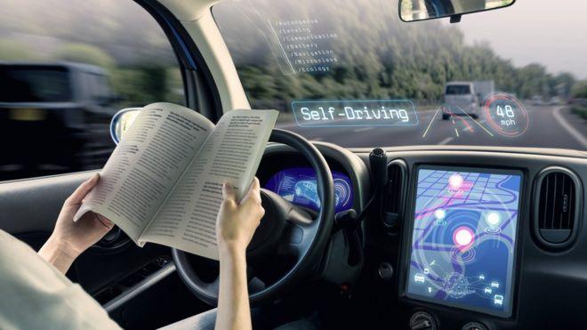 A person reading a book in an autonomous car