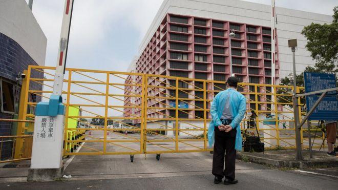 身穿疫病防護衣物的保安員在香港上水屠房外站崗(13/5/2019)