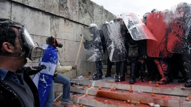 Протестующие противостоят полиции, которую облили краской