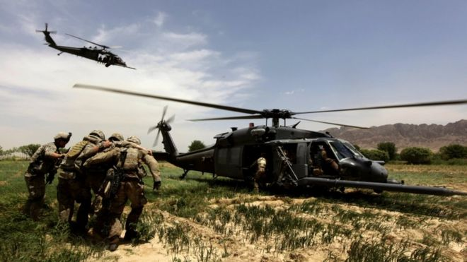 US troops leading a wounded soldier to a helicopter in Afghanistan, May 2010