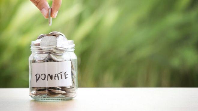 Una persona colocando una moneda en un frasco de donaciones