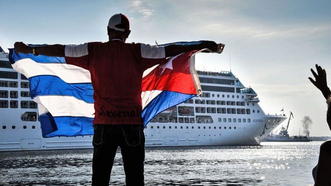 A man holds a Cuban flag with a cruise ship in the background