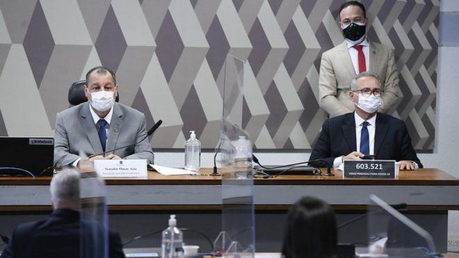 Senadores Omar Aziz e Renan Calheiros sentados lado a lado na mesa diretora da CPI da covid-19