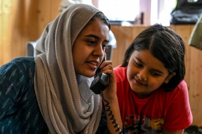 In this photo taken on August 17, 2019, Kashmiri Muslims talk to relatives on a landline phone in Srinagar