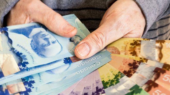 A man holding up Canadian dollar bills