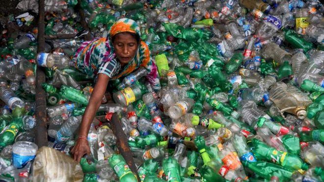 Una mujer en medio de botellas de plástico para reciclar.
