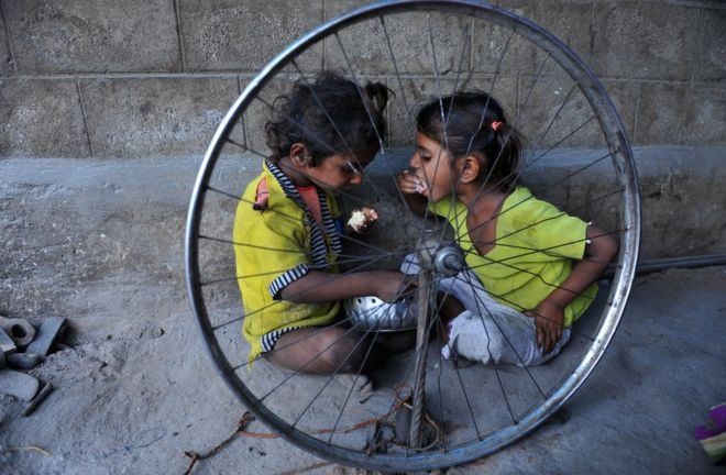 Two children eat at a temporary shelter