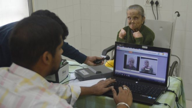 Officials take Sajida Begum's picture for her Aadhaar card