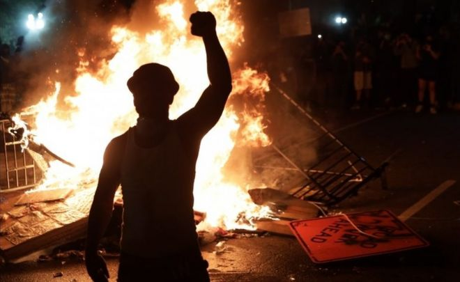 A protesters stands by a fire near the White House in Washington DC. Photo: 31 May 2020