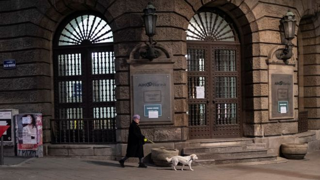 A woman walks her dog during a curfew imposed to prevent the spread of coronavirus disease in Belgrade