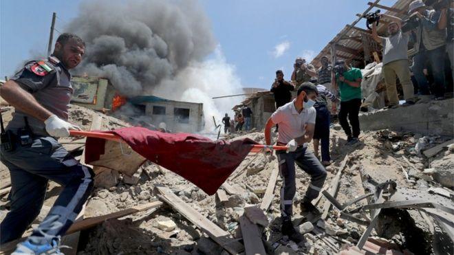 فلسطينيون يخلون جثة لقتيل من أحد المواقع الذي تعرض لقصف إسرائيل اليوم