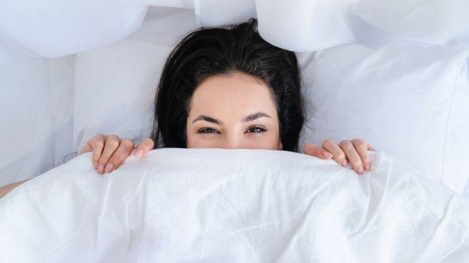 Una mujer debajo de las sábanas