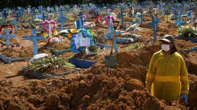 Homem com máscara abre novas covas em cemitério
