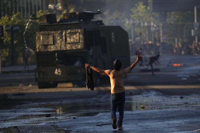 A man confronts a tank at protests in Chile