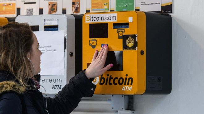 A woman touches an ATM machine for digital currency Bitcoin in Hong Kong on December 18, 2017.