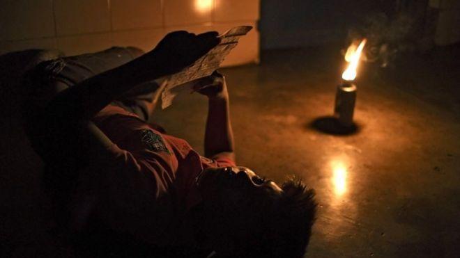 hombre lee a la luz de un mechero