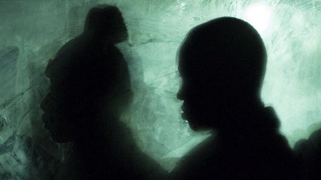 Silhouettes of two people inside a bus waiting to be transferred
