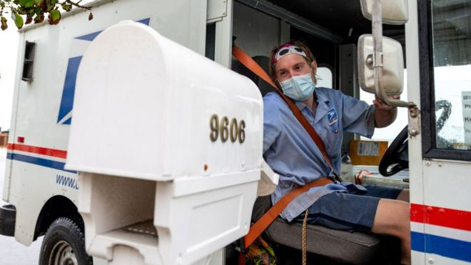 A postal worker delivers mail wearing a mask