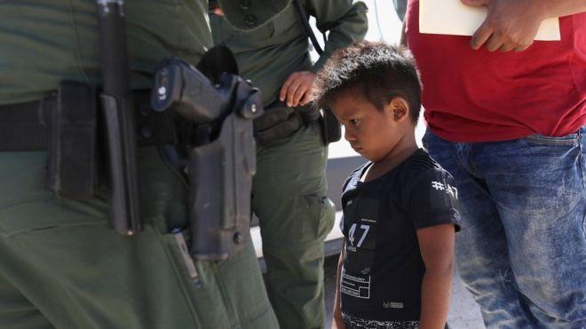 Niño de Honduras espera mientras él y su padre son detenidos por la patrulla fronteriza en Texas.