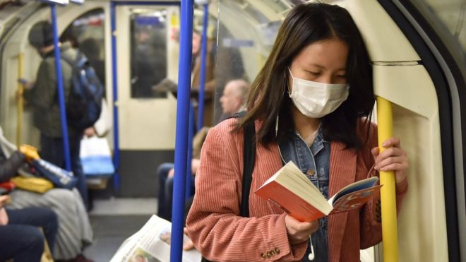 A woman wearing a mask on the London Underground
