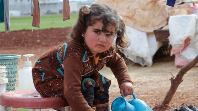 فتاة سورية تغسل الطين من حذائها في مخيم للنازحين في شرق معرة النعمان، شمالي إدلب السورية. 23 شباط 2020