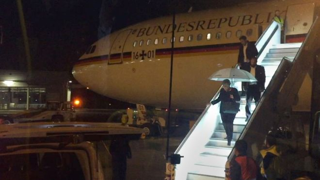 Angela Merkel emerges at Cologne airport from the Airbus A340 taking her to the summit