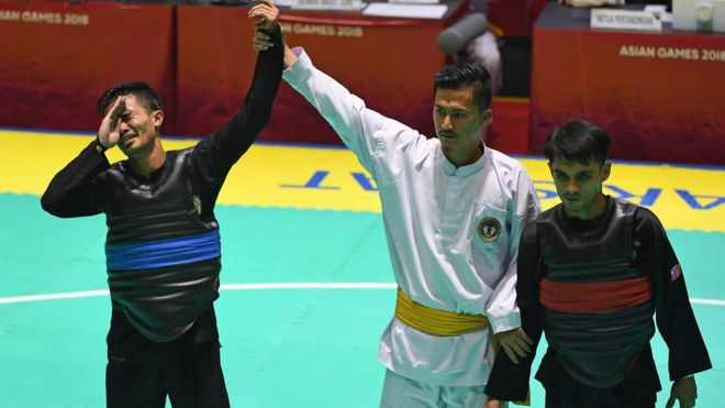 Pesilat Indonesia Abdul Malik (kiri) menangis usai dinyatakan menang atas pesilat Malaysia Muhammad Faizul M Nasir (kanan) dan meraih medali emas dalam babak final Kelas B Putra Asian Games 2018 di Padepokan Pencak Silat Taman Mini Indonesia Indah (TMII), Jakarta, Senin (27/8).