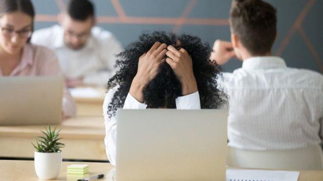 Mujer con las manos en la cabeza frente a un ordenador.