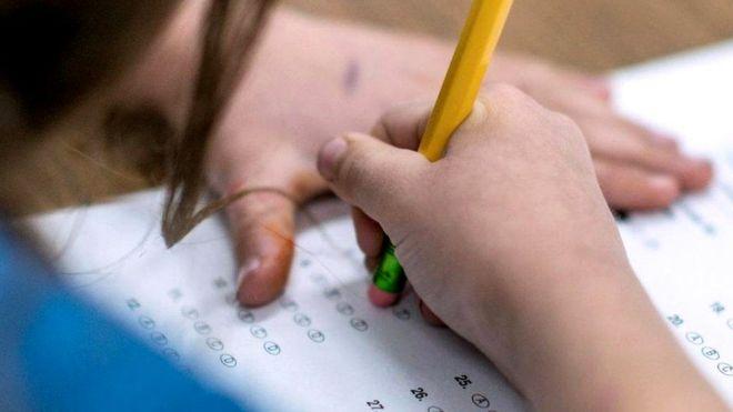 Девочка выполняет задание в школе