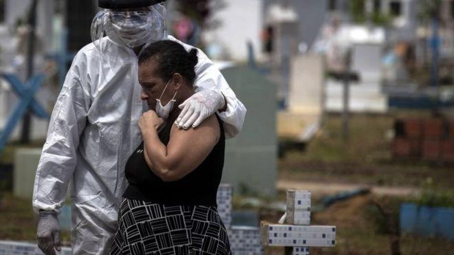 Mulher é consolada no cemitério