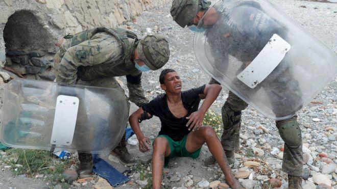 جنديان إسبانيان يحيطان بصبي مغربي وصل إلى سبتة سباحة