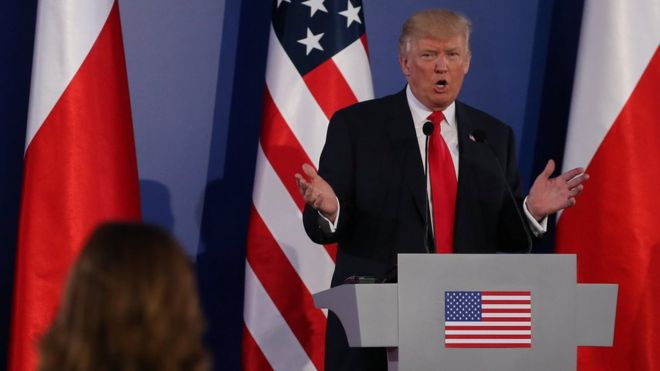 Donald Trump pictured at a podium in front of the US and Polish flags at a joint news conference in Warsaw