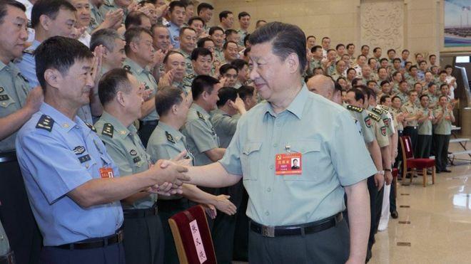 中央電視台播報了習近平穿軍裝講話,並和站立鼓掌的軍隊領導人握手的消息。