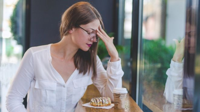Mujer que no se encuentra bien frente a café y dulce.