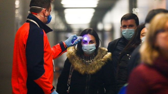 Passengers from Milano, Italy, have their temperatures checked at Krakow Airport in Balice, Poland
