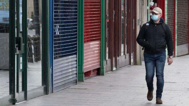 Man in mask walks past empty shops