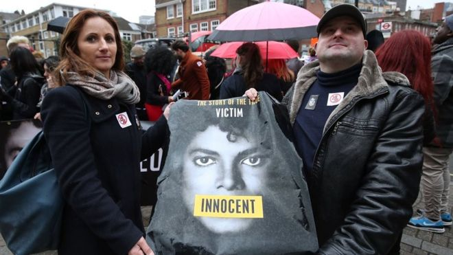 Dois fãs mostram camisa com rosto de Michael Jackson em protesto em defesa ao cantor em frente ao prédio da emissora Channel 4