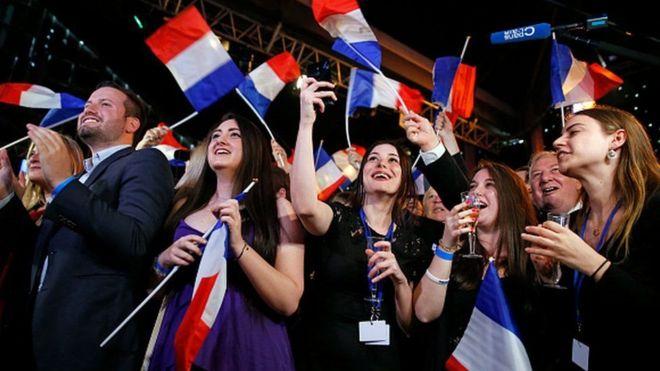 Votantes franceses con banderas de su país.