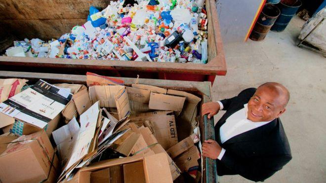 O empresário Júlio César Chagas Santos observa contêineres com material reciclado