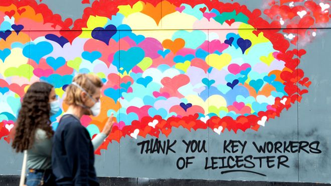 Two women walk past a mural in Leicester