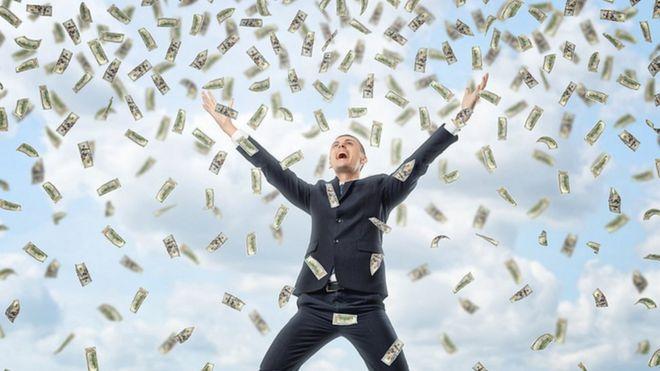 Homem debaixo de 'chuva de dinheiro'