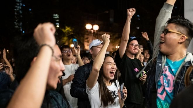 Pro-democracy supporters chant as they celebrate after pro-Beijing candidate Junius Ho lost a seat in the district council elections in Tuen Mun district of Hong Kong