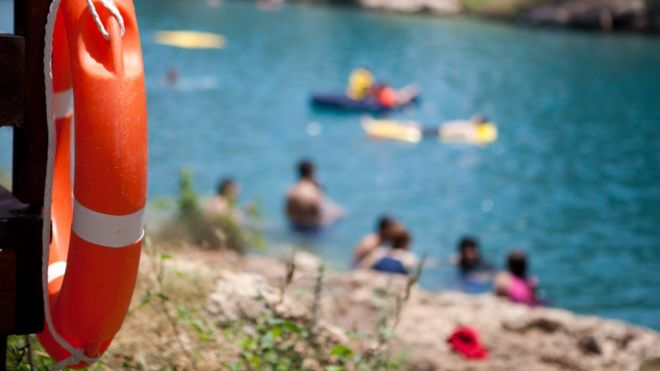 A bright orange life buoy hung on a dock overlooking a group of swimming people