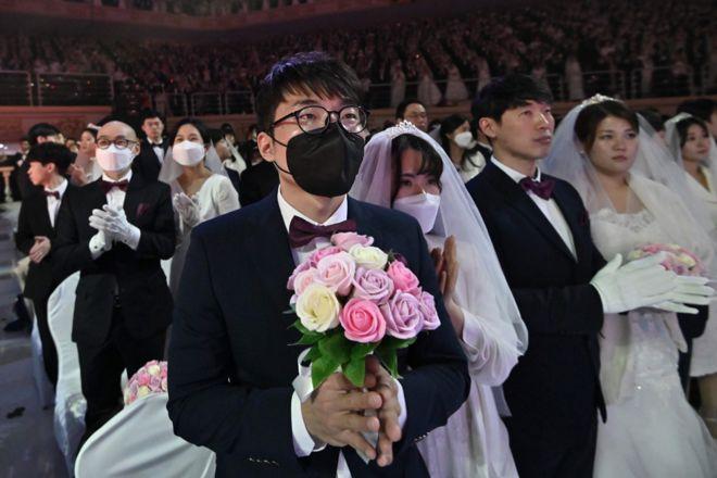زوجان يرتديان قناعان واقيان يشاركان في حفل زفاف جماعي نظمته كنيسة التوحيد في غابيونغ