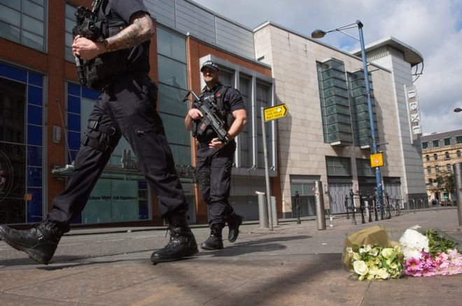 Armed police patrol walk past the first floral tributes to the victims of the terrorist attack on 23 May 2017 in Manchester, England.