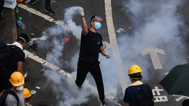A protester throws back a tear gas during clashes with police outside the government headquarters in Hong Kong on June 12, 2019