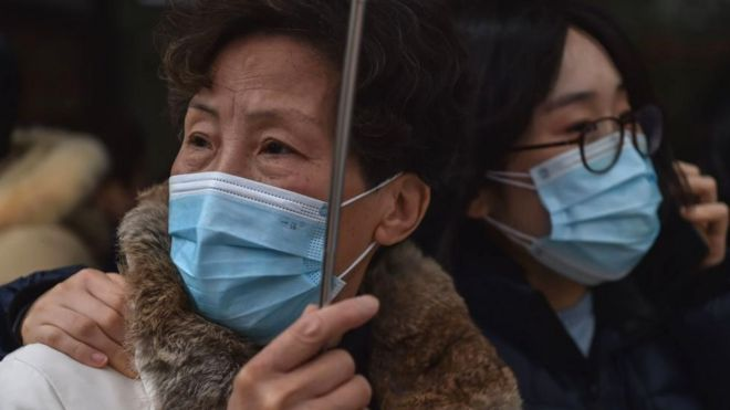 People wearing protective masks are seen outside a hospital in Shanghai o­n January 22, 2020