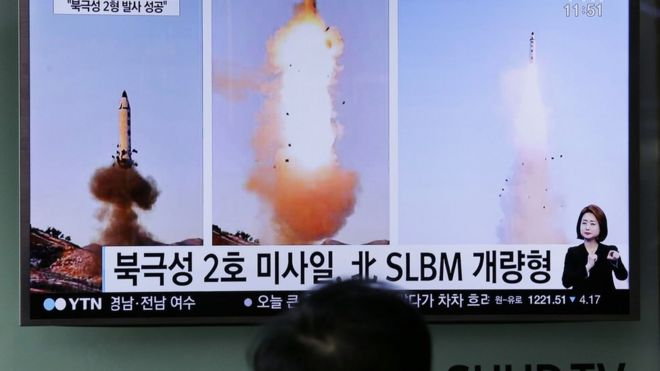 """A man watches a TV news program showing photos published in North Korea's Rodong Sinmun newspaper of North Korea's """"Pukguksong-2"""" missile launch at Seoul Railway station in Seoul, South Korea, Monday, 13 February 2017"""