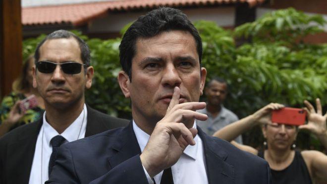Juiz Sergio Moro faz sinal de silêncio, com o dedo indicador erguido em frente à boca, ao chegar à residência de Bolsonaro, no Rio